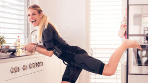 Eins sportliche junge Frau die EMS-Training zu Hause macht ist zu sehen. Sie befindet sich in der Küche und trägt den kabellosen EMS-Anzug von ANTELOPE. Die Frau ist blond und trägt die Haare zu einem Pferdeschwanz gebunden. Sie trägt den kabellosen EMS-ANzug von ANTELOPE und befindet sich in der Küche. In ihrer Hand hält sie den Griff einer Pfanne, die vor ihr auf einer einer weißen Küchenzeile steht. Sie steht auf einem Bein und streckt ihr linkes Bein im 90° Winkel nach hinten weg.