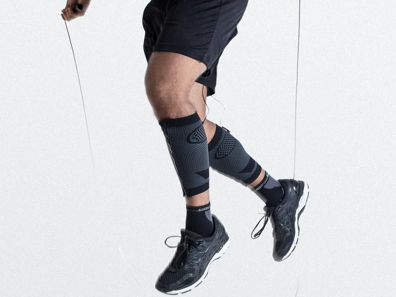 Ein junger Mann trägt die Elektro-Muskel-Stimulation (EMS) CALF-GUARDS von ANTELOPE und trainiert seine Waden durch Seilspringen. Man sieht ihn von der Hüfte abwärts. Der Hintergrund ist grau. Er trägt eine dunkle Hose.