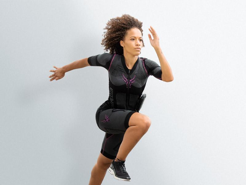 Eine junge Frau trägt den Elektro-Muskel-Stimulation (EMS) -Anzug von ANTELOPE. Sie springt dynamisch, ähnlich wie bei Sprint hoch. Der Hintergrund ist hellgrau.