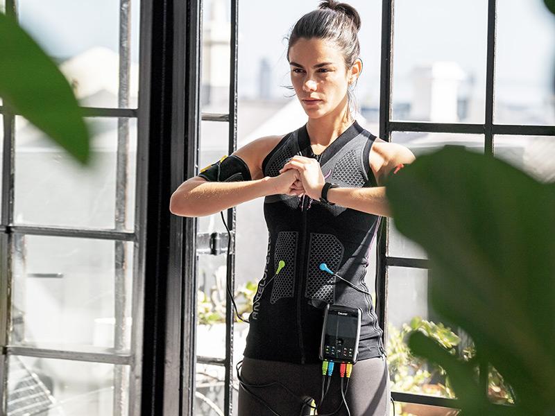 Eine Frau steht vor einem großen Fenster und presst die Hände zusammen. Sie trägt das ANTELOPE EMS TANK-TOP in Kombination mit dem EM 95 von Beurer.