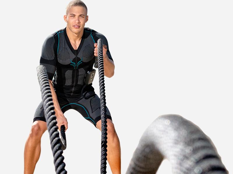 Ein junger Mann trainiert mit dem kabellosen EMS-Anzug von ANTELOPE mit schweren Seilen. Er sieht frontal in die Kamera, die Seile befinden sich vor ihm und er schlägt große Wellen mit ihnen. Der Hintergrund ist eine graue Fläche.