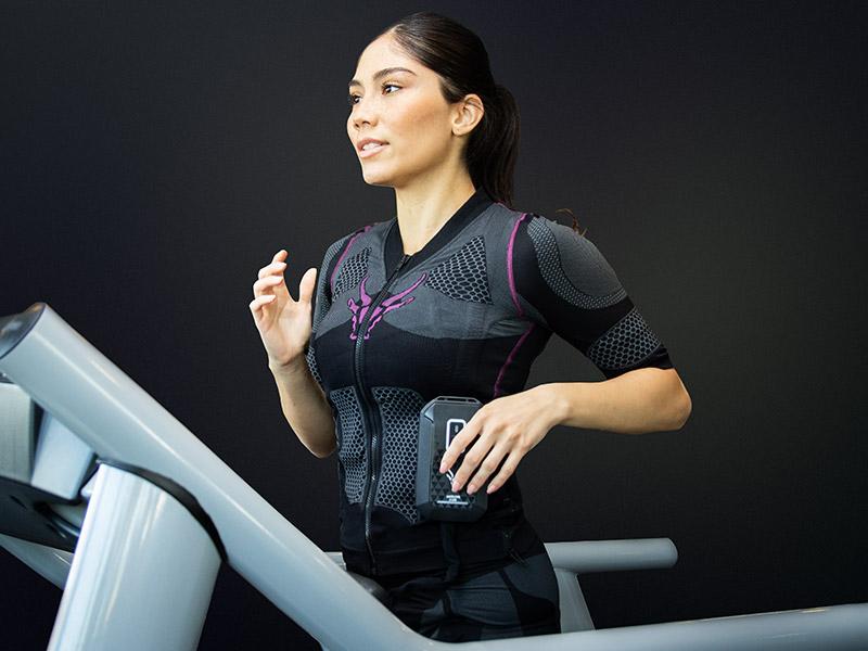 Eine junge Frau trägt den kabellosen EMS-Anzug von ANTELOPE. Sie läuft auf einem Laufband in einem dunklen Fitnessraum. Hinter Ihr sieht man eine schwarze Wand. Man sieht sie leicht von der Seite.