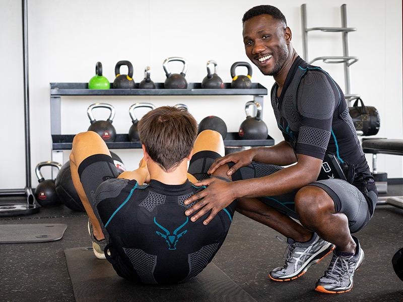 Zwei Männer, die den den kabellosen EMS-Anzug der Marke ANTELOPE tragen. Einer der jungen Männer trainiert auf dem Boden, auf einer schwarzen Trainingsmatte. Man sieht seinen Rücken und Hinterkopf, er führt eine Bauchpresse ohne Geräte aus. Auf dem Anzug sieht man an seinem Rücken das ANTELOPE Logo. Ein zweiter dunkelhäutiger junger Mann befindet sich in einer Hocke und berührt den ersten Mann an der Schuler. Er schaut zur Kamera und lächelt. Beide tragen den EMS-Anzug von ANTELOPE sie befinden sich in einem Fitnessraum.
