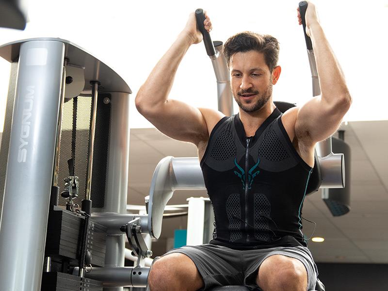 Ein junger sportlicher Mann trainiert seinen Rücken und Arme an einem Trainingsgerät . Er trägt das ANTELOPE EMS Tank-Top und befindet sich in einem Fitnessraum.
