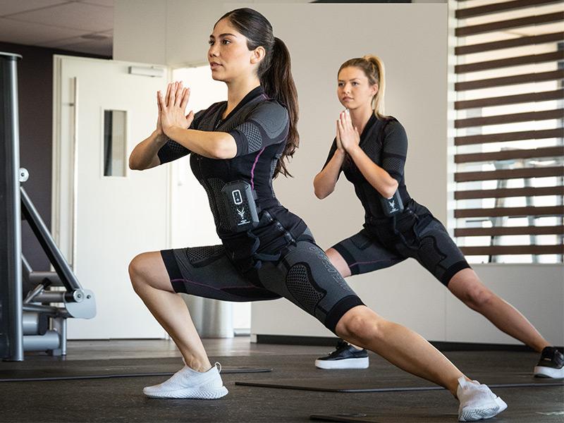 Zwei junge Frauen, trainieren in einem Fitnessraum. Sie tragen den kabellosen EMS-Anzug von ANTELOPE und führen einen Ausfallschritt aus.