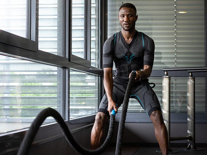 Ein junger Mann intensiviert sein Training mit den kabellosen EMS-Anzug von ANTELOPE. Er trainiert seinen Oberkörper an Seilen in einem dunklen Fitnessraum. Er führt mit den Seilen große Wellen aus.
