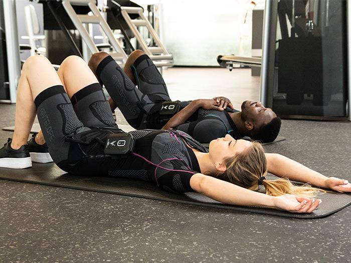 Ein junger Mann und eine junge Frau verkürzen ihre Regenerationszeit durch den kabellosen EMS-Anzug von ANTELOPE. Sie liegen beide auf dem Rücken auf den Boden in einem Fitnessraum und entspannen sich durch die Massagefunktion der ANTELOPE.APP.