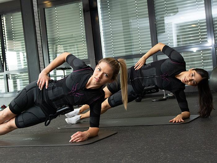 Zwei junge Frauen, trainieren in einem dunklen Fitnessraum. Sie tragen den ANTELOPE EMS-Anzug und führen einen seitlichen Stütz aus.