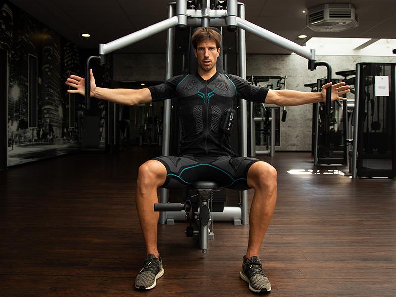 Ein junger Mann kombiniert Kraft mit EMS-Training. Er trägt den EMS-ANZUG von ANTELOPE und trainiert seine Arme und seinen Rücken an einem Butterfly-Fitnessgerät in einem dunkeln Fitnessraum. Man sieht ihn von vorne, er sitzt auf dem Gerät. Seine Arme sind zu den Seiten ausgestreckt mit abgespreizten Händen an den Griffen des Fitnessgerätes.