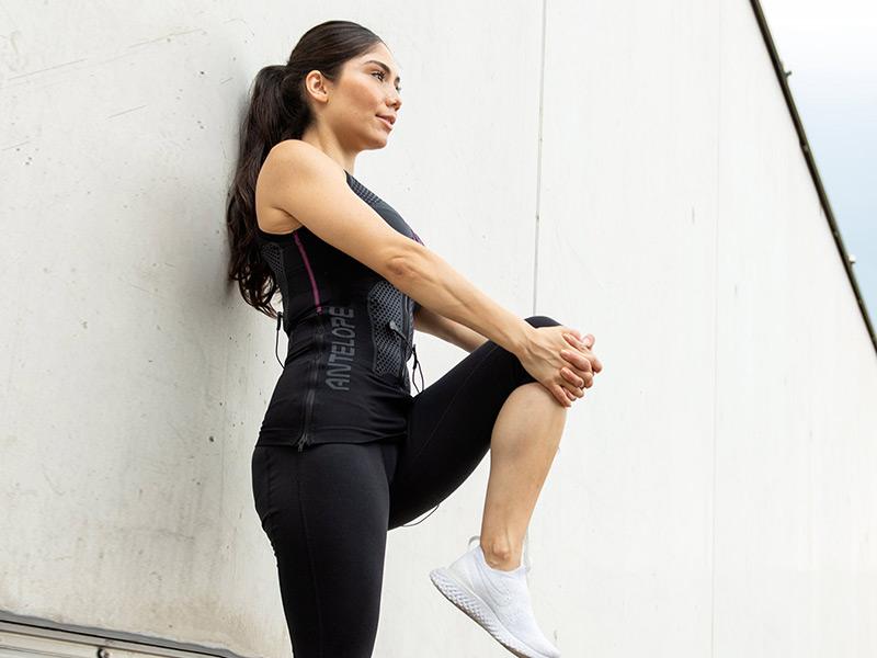 Eine schlanke junge Frau dehnt sich. Sie trägt das ANTELOPE EMS TANK-TOP und stützt sich an einer Wand ab. Sie zieht mit ihren Armen, vor ihrem Körper, ihr linkes Knie nach oben in Richtung Brust. Im Hintergrund sieht man eine weiße Wand und etwas blauen Himmel. Sie befindet sich auf einer Dachterrasse.
