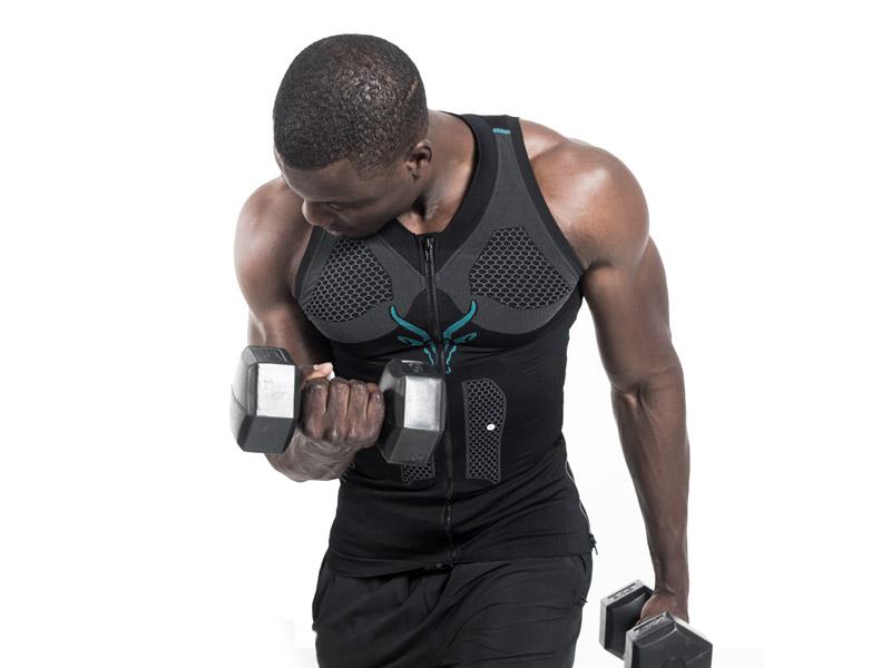 Ein junger Mann trainiert mit der mobile EMS-Weste von ANTELOPE. Er hält Hanteln in den Händen, sein linker Arm ist nach unten ausgestreckt. Mit seinem rechten Arm führt er Bizepscurls aus.
