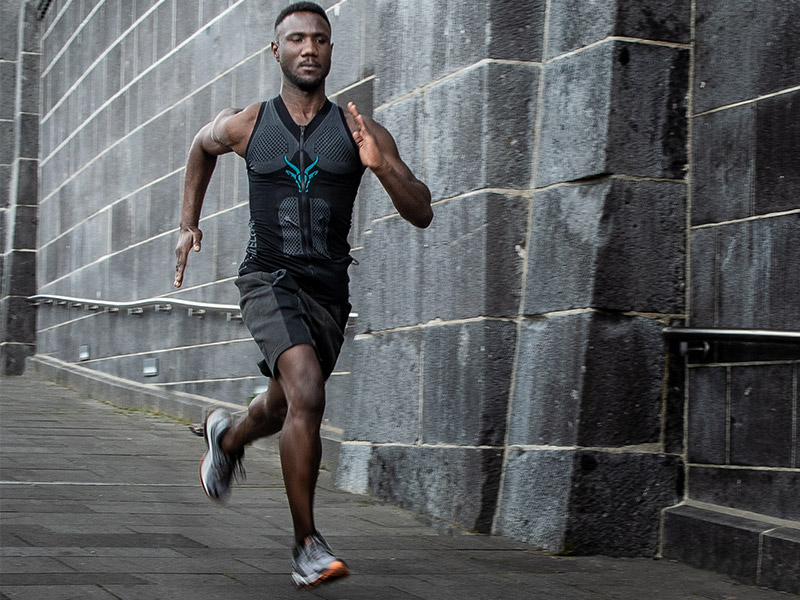 Ein junger Mann läuft schnell eine Straße hinunter er trägt die EMS-Weste von ANTELOPE, kombiniert mit einer kurzen dunklen Sporthose und Turnschuhe. Im Hintergrund sieht man eine dunkelgraue Steinwand. Die Straße ist ebenfalls dunkelgrau.
