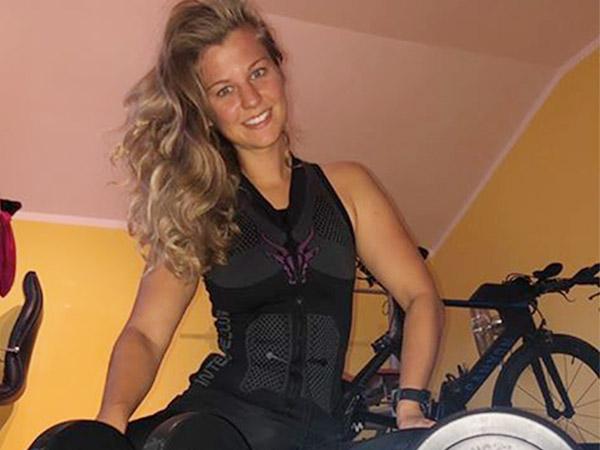 Kundenerfahrungen zum EMS-TANK-TOP von ANTELOPE. Eine junge Frau lächelt in die Kamera- sie trägt die EMS Weste von ANTELOPE und sitzt in einem kleinen Raum. Im Hintergrund stehen Fahrräder.