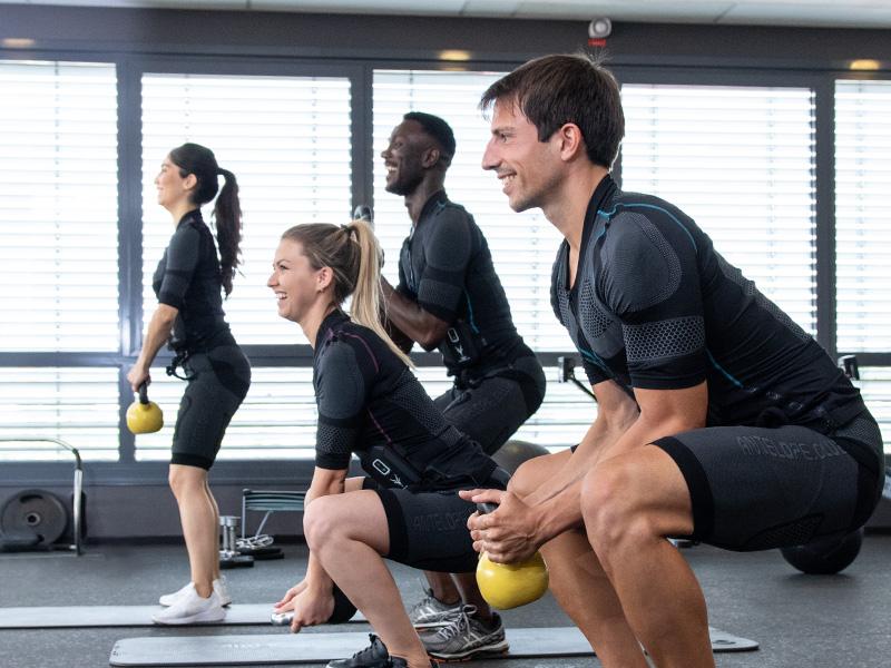 Eine Gruppe von jungen Menschen trainiert mit dem kabellosen EMS-System von ANTELOPE - den ANTELOPE.SUIT und Kettlebells, in in einem EMS-Studio. Sie stehen seitlich zur Kamera. In der Gruppe sind zwei Frauen und zwei Männer. Sie führen mit der Kettlebell in der Hand Kniebeugen aus.