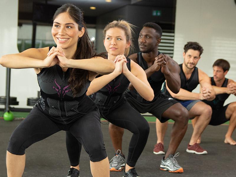Ein Team trägt die EMS-Weste von ANTELOPE und steht in einem Fitnessraum und machen EMS-Training. Alle führen eine tiefe Kniebeuge aus. Die Gruppe steht versetzt hintereinander und bestehen aus 5 Leuten. Zwei Frauen und 3 Männer. Die Frauen stehen vorne.