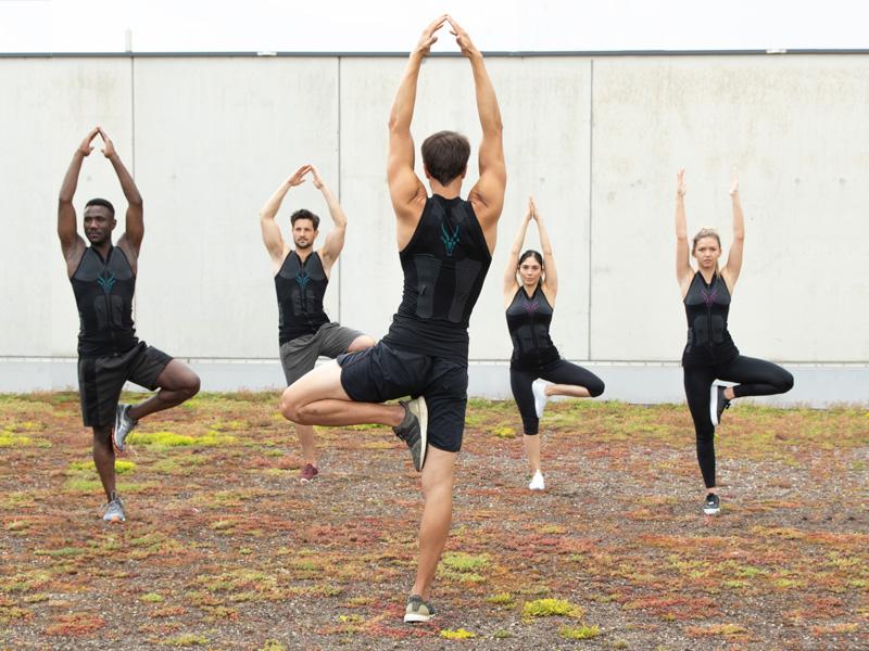 Eine Gruppe von Menschen trainiert zusammen mit der EMS-Weste von ANTELOPE. Sie stehen in einer Yoga Pose. Ein Bein ist angewinkelt und am anderen Oberschenkel abgestützt, ihre Hände sind ausgestreckt über ihrem Kopf in der Luft. Sie befinden sich auf einer Dachterasse. Eine Person steht im Vordergrund mit dem Rücken zur Kamera und weist die Gruppe an. Die anderen vier Personen stehen frontal zur Kamera und folgen den Anweisungen des Trainers.