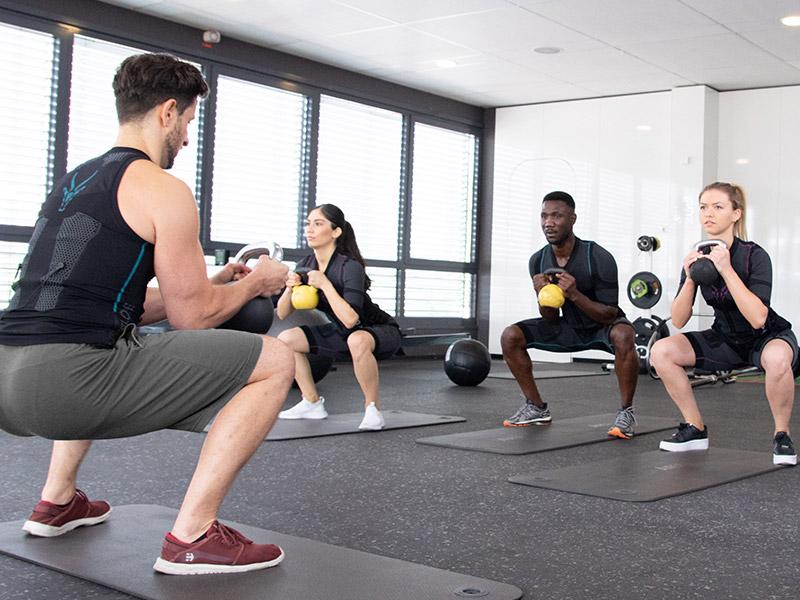 Eine Gruppe trägt den EMS-Anzug von ANTELOPE und trainiert zusammen in einem großem Fitnessraum. Ein Mann, der EMS-Trainer, steht vorne und führt eine Übung, Kniebeugen mit Kettlebells, vor. Er trägt die EMS-Weste von ANTELOPE.
