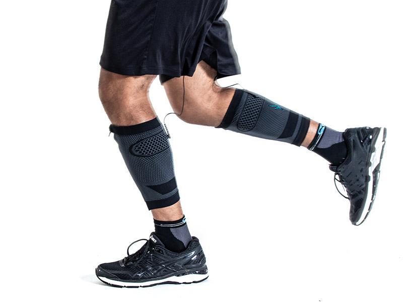 Ein junger Mann trainiert beim Laufen seine Waden mit den EMS CALF-GUARDS von ANTELOPE. Man sieht nur seine Beine. Er trägt eine kurze schwarze Hose und Turnschuhe. Der Hintergrund ist eine weiße Fläche.