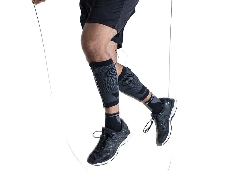 Ein junger Mann trainiert beim Seilspringen seine Sprungkraft mit den EMS-CALF-GUARDS von ANTELOPE. Man sieht einen Ausschnitt seiner Beine von den Oberschenkeln bis zu den Turnschuhen. Er trägt die ANTELOPE CALF-GUARDS, eine kurze schwarze Hose und Turnschuhe.