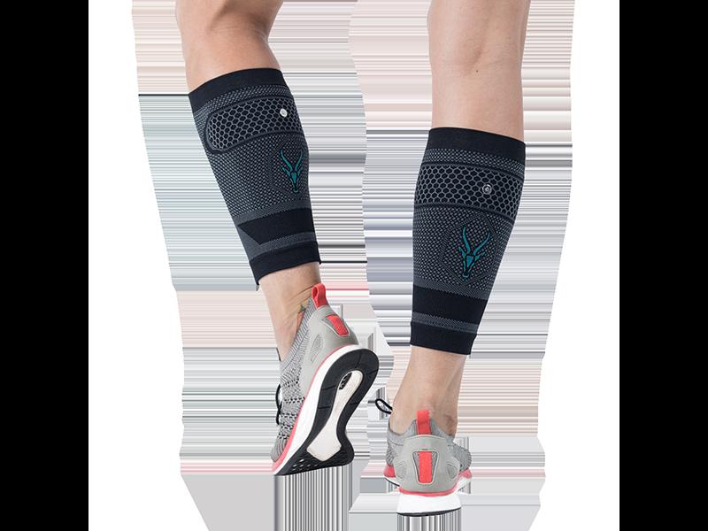 Ausschnitt von Beinen einer jungen Frau von hinten mit den ANTELOPE EMS CALF-GUARDS. Das ANTELOPE Logo ist zentral auf der Textilie. Die ANTELOPE.CALF-GUARDS sind Kompressions Stulpen mit EMS fürs Wadentraining. Die Beine sind leicht angewinkelt. Die junge Frau trägt Sportschuhe. Der Hintergrund ist schwarz.