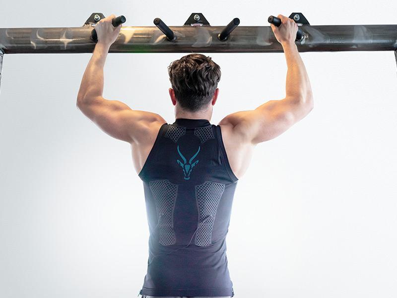 Ein junger Mann trägt das Elektro-Muskel-Stimulation (EMS) -TANK-TOP von ANTELOPE und zieht sich an einer Stange hoch. Mann sieht seinen Rücken und muskulösen Arme. Auf dem Rücken der EMS-Weste ist das Logo von ANTELOPE zusehen. Der Hintergrund ist hellgrau.
