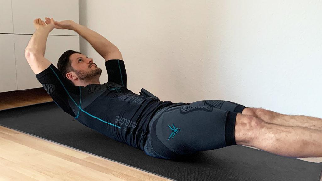 Ein sportlicher junger Mann der EMS-Training zu Hause macht ist zu sehen. Er liegt auf dem Boden, auf einer schwarzen Fitnessmatte. Er trägt den kabellosen EMS-Anzug von ANTELOPE und führt eine Übung zum Training der Bauchmuskulatur aus. Seine Arme sind über den Kopf gestreckt und die Schultern heben vom Boden ab. Auch die Beine sind vom Boden gelöst. Der Körper des jungen Mannes steht unter Anspannung.