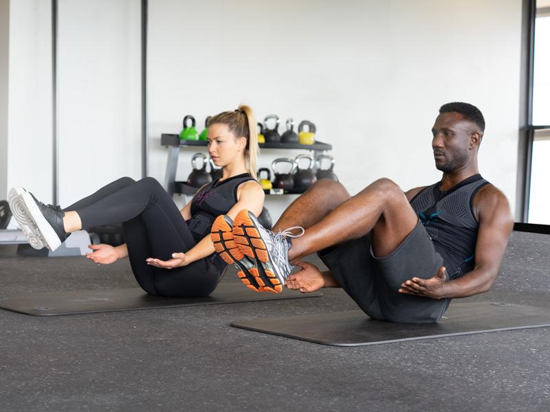 Eine junge Frau und ein junger Mann tragen die mobile EMS-Weste von ANTELOPE und trainieren ihren Bauch. Sie sitzen auf dunklen Yogamatten auf dem Boden. Ihre Beine sind vom Boden angehoben. Sie befinden sich in einem Fitnessraum. Im Hintergrund sieht man eine Band mit Kettlebells.