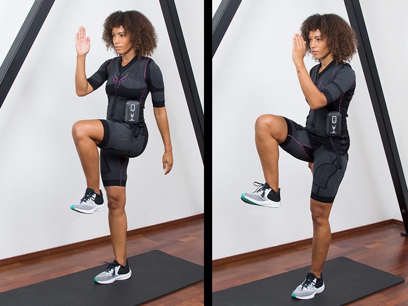 """Zu sehen ist eine sportliche junge Frau die EMS-Training zu Hause macht. Die junge Frau hat dunkelbraune Haare und dunkle Augen. Sie steht auf einer schwarzen Fitnessmatte. Sie trägt den EMS-Anzug von ANTELOPE und führt die Übung """"Kniehub"""" aus. Es ist eine Bewegungsabfolge bestehend aus 2 Bildern zu sehen. In Abbildung 1 befindet sie sich im hüftbreiten Stand auf einer schwarzen Fitnessmatte. Das linke Knie zieht im rechten Winkel in Richtung Brust, ihren rechten Ellenbogen führt sie dabei in Richtung Knie. In Abbildung 2 ist die gleiche Ausführung mit dem rechten Bein zu sehen, das nun zum linken Ellenbogen zieht. In den Abbildungen ist am unteren Ende ein schwarzer Balken zu sehen mit einer weißen Schrift."""