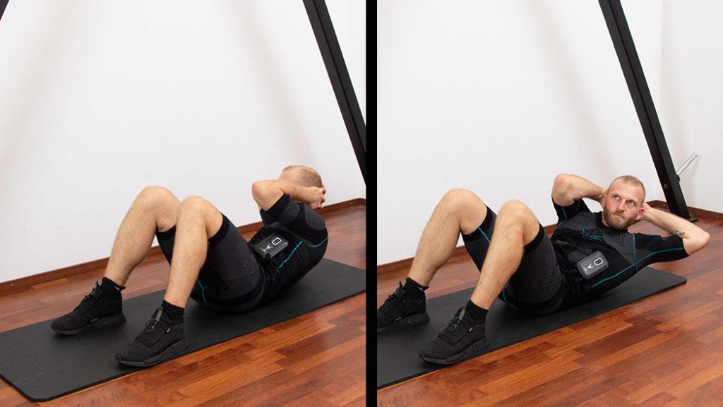 """Es sind 2 Abbildungen einer Übungsabfolge zu sehen. Ein sportlicher junger Mann der EMS-Training zu Hause macht. Der junge Mann hat dunkelblonde Haare und blaue Augen. Er liegt auf einer schwarzen Fitnessmatte. Er trägt den EMS-Anzug von ANTELOPE, trägt schwarze Sportschuhe und führt die Übung """"Sit-Ups"""" aus, eine Übung zum Training der Bauchmuskulatur. In Abbildung 1 befindet er sich liegend auf der Matte. Seine Hände befinden sich hinter dem Kopf, die Ellenbogen zeigen nach außen und die Schultern heben vom Boden ab. Die Beine sind angewinkelt. Er führt den linken Ellenbogen zum rechten Knie. In Abbildung 2 führt der Mann die gleiche Übung mit der anderen Seite durch. In den Abbildungen ist am unteren Ende ein schwarzer Balken zu sehen mit einer weißen Schrift. In der rechten Ecke des schwarzen Balken ist in weißer Schrift """"3 Sätze, 15 Wdh."""" zu sehen."""