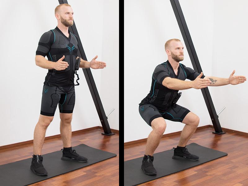 """Es sind 2 Abbildungen einer Übungsabfolge zu sehen. Ein sportlicher junger Mann der EMS-Training zu Hause macht. Der junge Mann hat dunkelblonde Haare und blaue Augen. Er führt die Übung """"Squat"""" aus. In der 1. Abbildung steht er hüftbreit auf einer schwarzen Fitnessmatte und hat die Arme seitlich im neunzig Grad Winkel ausgestreckt. In der 2. Abbildung geht der Mann aus dem hüftbreiten Stand mit dem Gesäß senkend bis auf Kniehöhe in die Hocke. Er trägt den EMS-Anzug von ANTELOPE und dazu schwarze Sportschuhe und schaut fokussiert nach Vorne."""