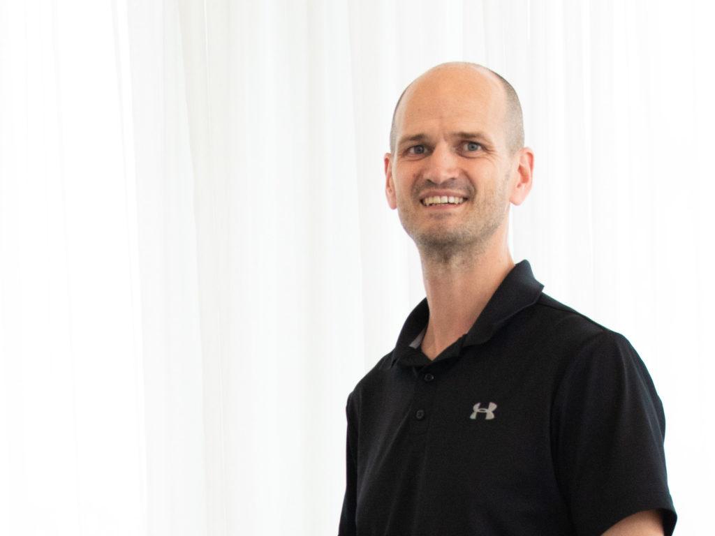 """Der Autor des Beitrags """"Vorsätze für 2021"""" Dr. Lutz Graumann ist zu sehen. Er steht vor einem weißen Vorhang und lächelt in die Kamera. Dr. Graumann hat eine Glatze, der Haaransatz lässt erahnen, dass er dunkle Haare hat. Seine Augen sind blau. Er trägt ein schwarzes Poloshirt auf dem ein weißes Logo oberhalb der rechten Brust platziert ist."""