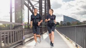 Passend zu dem Thema Vorsätze für 2021 ist eine sportliche junge Frau und ein sportlicher junger Mann zu sehen. Sie joggen auf einer Brücke an Bahnschienen vorbei, die zu ihrer linken Seite zu sehen sind. Auf der rechten Seite befindet sich ein Geländer. Die Frau ist blond und trägt die Haare zu einem Pferdeschwanz gebunden. Sie trägt den EMS-Anzug von ANTELOPE und schwarze Sneaker. Der Mann hat dunkle Haare, sehr kurze Haare. Auch er trägt den EMS-Anzug von ANTELOPE. Die junge Frau und der junge Mann schauen sich lächelnd an. Im Hintergrund sind Bäume und ein großes Bürogebäude zu sehen, das die Form eines Dreiecks hat.