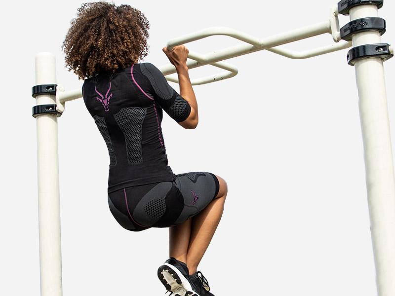 Eine junge Frau trägt den kabellosen EMS-Anzug von ANTELOPE und zieht sich an einer Stange hoch. Ihre Beine sind vor ihrem Körper im 90 Grad Winkel angewinkelt. Man sieht sie von Hinten. Das ANTELOPE Logo sieht man auf dem Rücken des ANTELOPE.SUITs. Die Stangen sind weiß und der Hintergrund hellgrau.