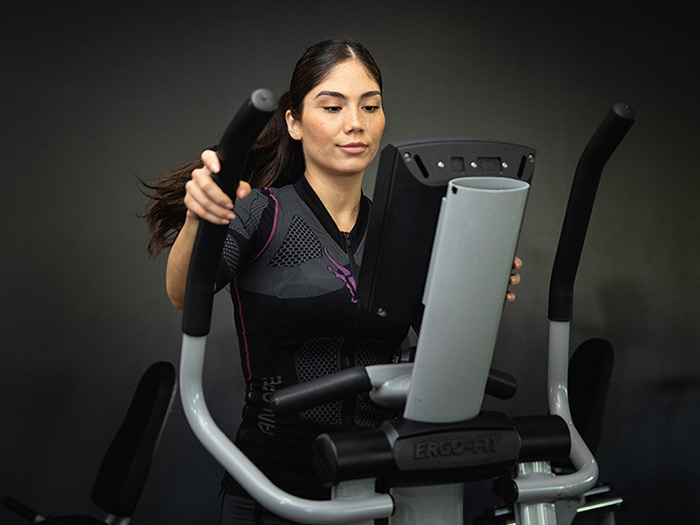 A young woman is wearing the wireless EMS suit by ANTELOPE and is doing a workout on a cross trainer in a dark room. The ANTELOPE.SUIT allows her to control her muscles individually during EMS training.