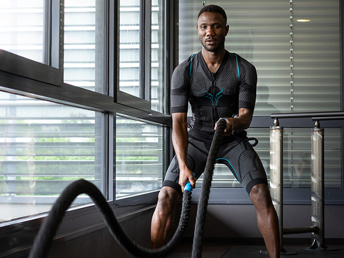 A young man intensifies his training with the wireless EMS suit from ANTELOPE. He is doing a workout for his upper body with battle ropes in a dark fitness room. He is performing big waves with the ropes.