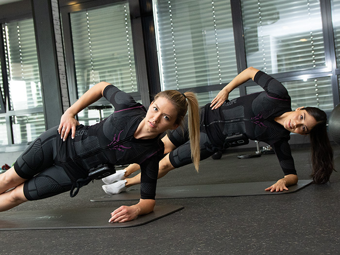 Two young women are exercising in a dark gym. They are wearing the EMS suit by ANTELOPE and performing a lateral raise.
