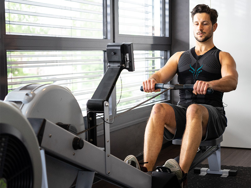 A young man is training his back on a traction device with the EMS vest from ANTELOPE. He is in a bright fitness room. He is sitting on the traction device and holds the bar of the device which is placed in front of him. He is pushing himself backwards off the machine by using his legs. You can see the front of the young man. You can see a wall and a window front in the background.