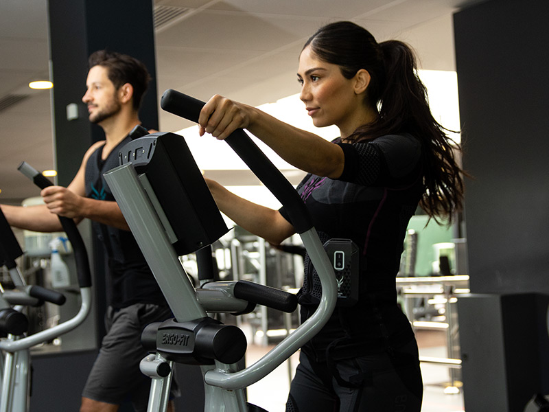 A young woman and a young man are working out with the ANTELOPE EMS products on a crossfit trainer in a fitness studio. The woman is working out with the EMS suit from ANTELOPE, the man with the EMS vest. The EMS training additionally boosts their metabolism. In the background you can see more fitness equipment.