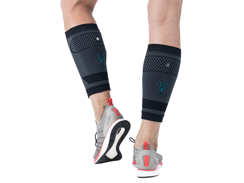 Detail of a young woman's legs from behind with the ANTELOPE EMS CALF-GUARDS. The ANTELOPE logo is placed in the center of the textile. The ANTELOPE.CALF-GUARDS are compression cuffs with EMS for calf training. The legs are slightly bent. The young woman is wearing sports shoes. The background is black.