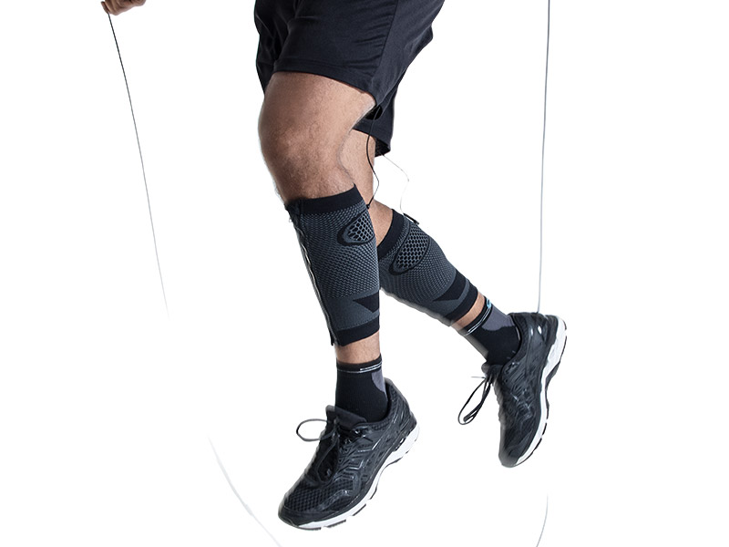A young man is training his bounce while jumping rope with the EMS CALF-GUARDS by ANTELOPE. You can see a section of his legs from his thighs to his trainers. He is wearing the ANTELOPE.CALF-GUARDS, black shorts and trainers.