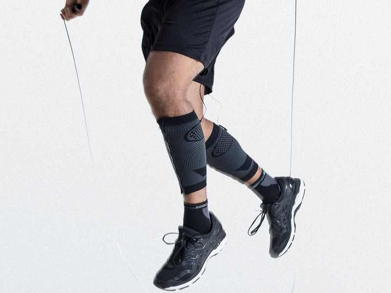 A young man wears ANTELOPE's electro-muscle stimulation (EMS) CALF-GUARDS and trains his calves by jumping rope. He is seen from the waist down. The background is grey. He is wearing dark trousers.