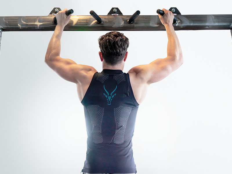 You can see a young man who is wearing the electro muscle stimulation (EMS) tank-top by ANTELOPE. He pulls himself up on a bar. You can see his back and muscular arms. The ANTELOPE logo is on the back of the EMS vest. The background is light grey.