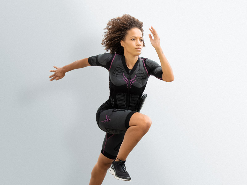 You can see a young woman wearing the electro muscle stimulation (EMS) suit from ANTELOPE. She is jumping up dynamically, similar to sprinting. The background is light grey.