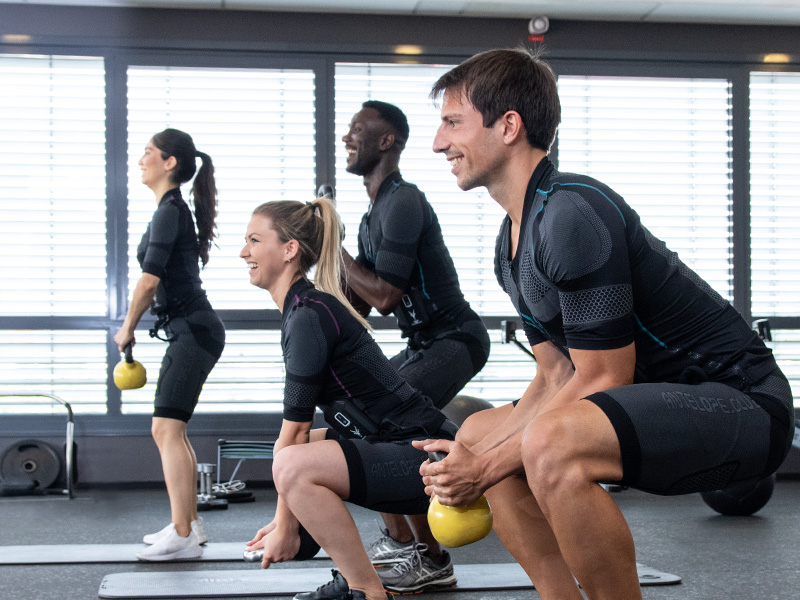 A group of young people are working out with a wireless EMS system - the ANTELOPE.SUIT and kettlebells, in an EMS studio. They are facing the camera sideways. There are two women and two men in the group. They are performing squats with the kettlebell in their hands.