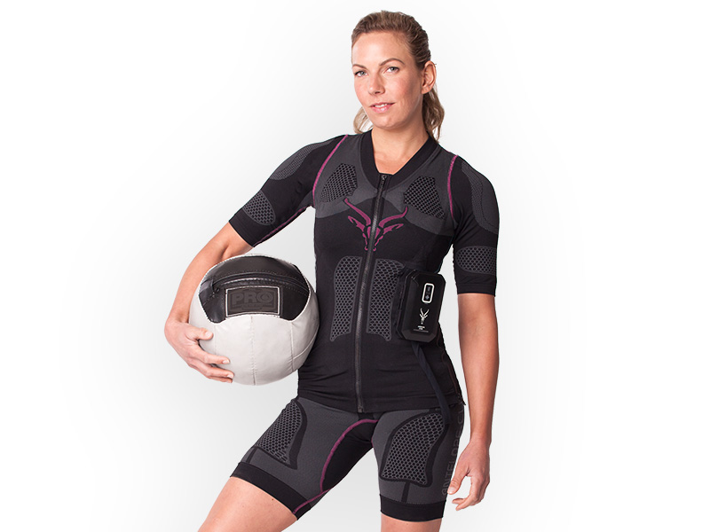 A young woman is wearing ANTELOPE's wireless EMS system, the ANTELOPE.SUIT. She is holding a medicine ball under her left arm and is looking straight into the camera.The background is white.