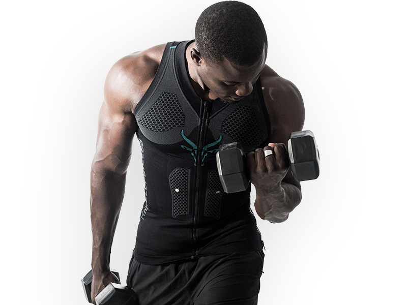 A young man is wearing the ANTELOPE.TANK-TOP and is holding dumbbells in his hands. He is performing a bicep curl with one arm. The background is a white surface. He looks sideways down at the dumbbell.