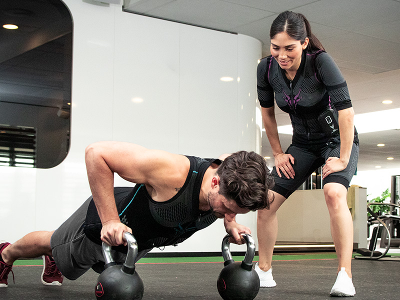 A young man is training with a wireless EMS system - the EMS-TANK-TOP by ANTELOPE, together with a personal trainer in an EMS studio. The young man performs push-ups with kettlebells. The personal trainer stands beside him and watches the execution of the exercise. She is wearing the EMS suit from ANTELOPE. In the background you can see the ceiling and walls of the gym.