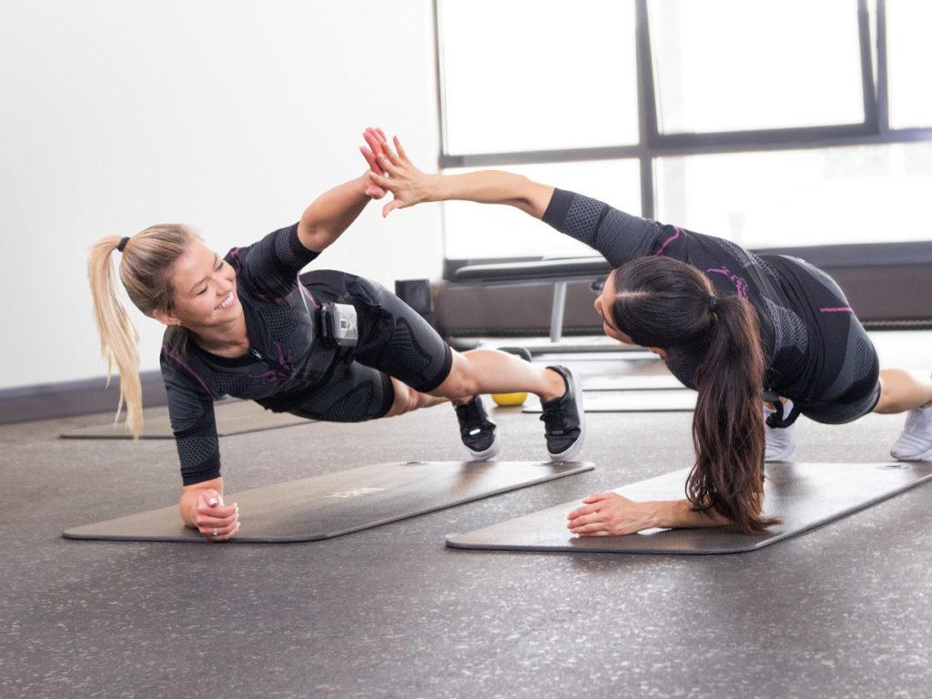 Zwei junge sportliche Frauen trainieren mit dem kabellosen ANTELOPE EMS Anzug. Sie befinden ich in einem Fitnessstudio. Beide Frauen befinden sich in einem Plank. Sie sehen sich gegenseitig an und klatschen sich ab. Im Hintergrund sieht meine eine Fensterfront. Der Boden ist dunkel